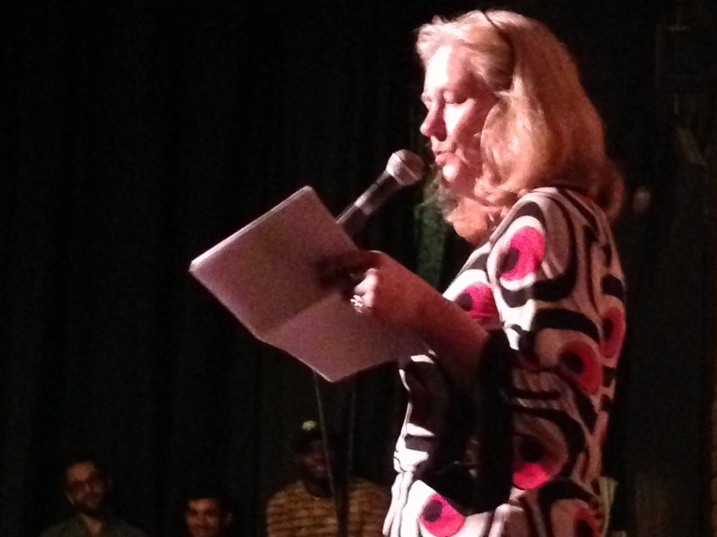 The poet Sarah Browning is seen from the side, reading from papers in front of a microphone. Her hair is reddish and to her shoulders. An audience is in the background